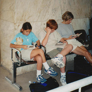 Jenny Moss and her children reading in a train station in Pisa, Italy